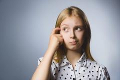 查寻用在面孔的手的特写镜头体贴的女孩反对灰色背景 免版税库存图片