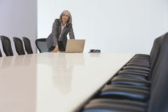 查寻由膝上型计算机的女实业家在证券交易经纪人行情室 免版税库存图片