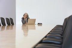 查寻由膝上型计算机的女实业家在证券交易经纪人行情室 免版税库存照片