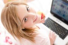 查寻美丽的柔和的甜少妇蓝眼睛女孩在床上与膝上型计算机和的苹果特写镜头画象  免版税库存照片