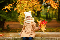 查寻,在的秋天的一件米黄外套的小俏丽的女孩 库存图片