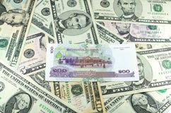 柬埔寨瑞尔(KHR)在许多美元背景 库存图片