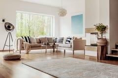 柳条无背长椅和一盏工业落地灯在明亮的客厅内部与别致的装饰和木元素 免版税库存照片