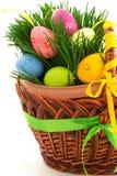 柳条木篮子用复活节彩蛋和新鲜的草,零件,为 库存照片