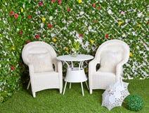 柳条白色家具在开花的庭院里 免版税库存图片