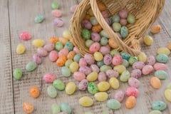 从柳条筐溢出的明亮地色的复活节彩蛋糖果 免版税库存图片