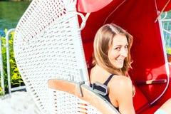 柳条长凳椅子的妇女 免版税图库摄影