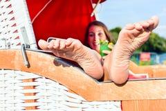 柳条长凳椅子饮用的鸡尾酒的妇女 免版税库存照片