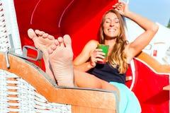 柳条长凳椅子饮用的鸡尾酒的妇女 免版税库存图片