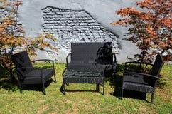 黑柳条露台家具在一个灰色砖墙前面的庭院里 免版税图库摄影