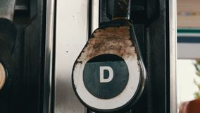 柴油的老被毁坏的生锈的燃料喷嘴在加油站垂悬紧密看法 股票录像