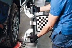 栅格传感器设置汽车的技工 与传感器轮子的汽车立场对准线反挠度的登记服务车间  库存照片
