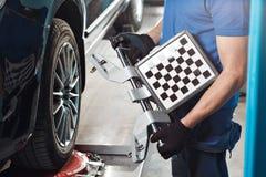 栅格传感器设置汽车的技工 与传感器轮子的汽车立场对准线反挠度的登记服务车间  免版税库存照片