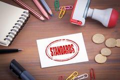 标准邮票 有文具、金钱和a的木办公桌 图库摄影