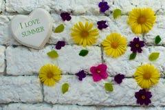 标志'我爱夏天'在心脏对一个白色砖墙和许多小花 图库摄影