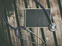 标志和听诊器在医疗和健康生活概念的桌理想放置 免版税库存照片