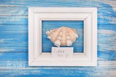 标志在一个白色框架的我爱你和海壳-葡萄酒样式 库存照片