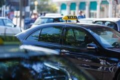 标志或标志与出租汽车的题字位于一个汽车屋顶在隐隐绰绰的背景城市街道和空白上 免版税库存图片