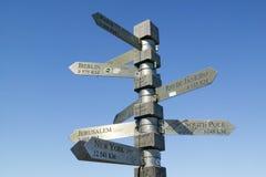 标志指向与英里共计到柏林,耶路撒冷,纽约,南极,巴黎,开普角的,好望角里约热内卢 库存图片