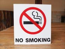 标志禁烟在桌上的白色背景 免版税图库摄影