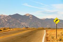 标志警告正确的曲线向前在一条山路在Colora 图库摄影