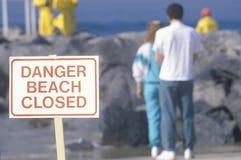 标志警告, dangerï ¿ ½海滩在背景中关闭了与人 免版税库存图片