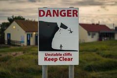 标志:危险不稳定的峭壁清楚地保持 库存照片