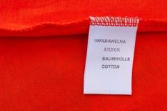 标签100%棉花 在不同的语言的题字:俄语,波兰语,英语,德语 免版税图库摄影