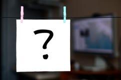标记问题 笔记在垂悬机智的一个白色贴纸被写 免版税库存照片