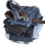 栈与棕色传送带的蓝色牛仔裤 免版税库存照片