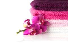 栈五颜六色的毛巾和紫色兰花开花 免版税库存图片
