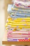 栈包扎的范围 角落特写镜头一个被放置的色的洗衣店 各种各样的颜色被折叠的亚麻布堆  免版税库存图片