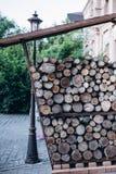 栈干木柴 向外餐馆在老镇 老大厦、绿色灌木和灯笼在背景 库存图片