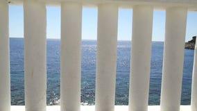栏杆的支海滩 俯视海的白色专栏 在蓝色海的白色柱子看法和horizont和天空在背景中 股票录像