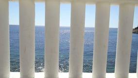 栏杆的支海滩 俯视海的白色专栏 在蓝色海的白色柱子看法和horizont和天空在背景中 股票视频