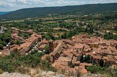 树、房子屋顶和钟楼看法在Moustiers Sainte玛里 免版税图库摄影