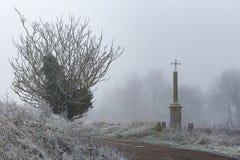 树、雾和十字架,冬天风景 免版税库存图片