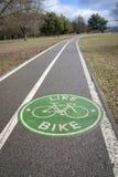 树之间的自行车道路由河 免版税库存照片