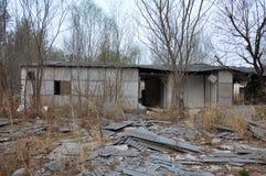 树包围的被放弃的房子 库存照片