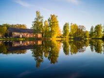树反射在湖在一个晴朗的春日-秋天Colou 库存图片