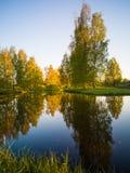 树反射在湖在一个晴朗的春日-秋天Colou 图库摄影