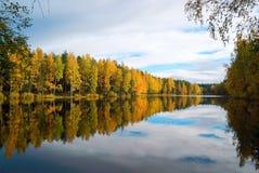 树和天空的镜象反射在湖 秋天横向 库存图片