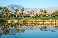 树和山的反射在高尔夫球场 库存照片