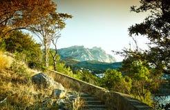 树和海日落的 蓝色克里米亚小山横向赤裸天空 免版税图库摄影