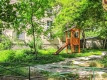树在城市在居民住房附近停放 儿童比赛的` s操场 库存图片