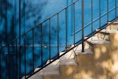树在黄色台阶和蓝色木墙壁遮蔽 免版税库存照片
