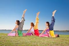 树夫妇、男人和妇女实践瑜伽asana 免版税库存照片