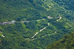 树木丛生的山坡路 免版税库存照片