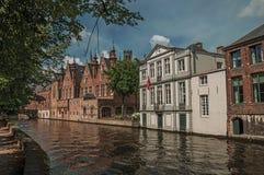 树木繁茂的庭院和砖瓦房在运河` s在一个晴天渐近在布鲁日 免版税库存照片