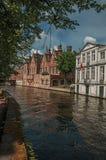 树木繁茂的庭院和砖瓦房在运河` s在一个晴天渐近在布鲁日 库存图片